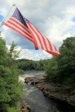 Bandiera americana che ondeggia sopra le acque infuriantesi del fiume Fotografia Stock