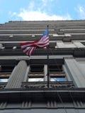 Bandiera americana che ondeggia un giorno ventoso, vista da sotto, davanti alla facciata storica dell'edificio per uffici immagini stock libere da diritti