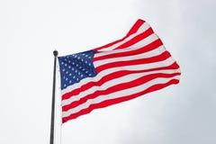 Bandiera americana che soffia in vento il giorno nuvoloso Fotografia Stock Libera da Diritti