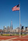 Bandiera americana che sta alta in Liberty State Park, NJ, con la vista di architettura moderna di Manhattan, NY Fotografia Stock