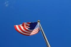 Bandiera americana contro chiaro cielo blu Immagini Stock Libere da Diritti