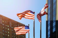 Bandiera americana contro la bandiera americana luminosa del cielo blu contro il cielo ed i grattacieli Immagini Stock
