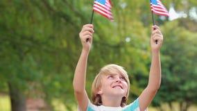 Bandiera americana d'ondeggiamento del ragazzino nel parco archivi video