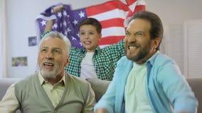 Bandiera americana d'ondeggiamento del ragazzo, famiglia che guarda la partita nazionale della squadra di football americano a ca video d archivio