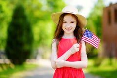 Bandiera americana d'uso della tenuta del cappello della bambina adorabile all'aperto il bello giorno di estate Immagini Stock Libere da Diritti