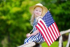 Bandiera americana d'uso della tenuta del cappello della bambina adorabile all'aperto il bello giorno di estate Fotografia Stock