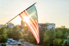 Bandiera americana dalla finestra su un fondo di tramonto Fotografia Stock Libera da Diritti