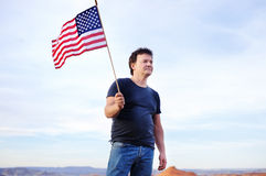 Bandiera americana della tenuta dell'uomo e distanza considerare Fotografie Stock