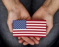 Bandiera americana della tenuta della donna sulle sue palme Fotografie Stock Libere da Diritti