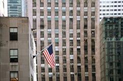 Bandiera americana di stelle e strisce contro le facciate della costruzione immagini stock