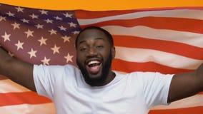 Bandiera americana maschio felice della tenuta del patriota su fondo giallo, festa dell'indipendenza video d archivio