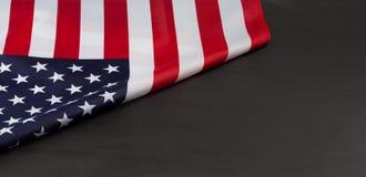 Bandiera americana piegata sulla lavagna nera Fotografie Stock