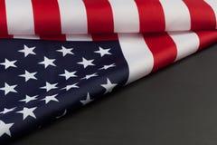Bandiera americana piegata sulla lavagna nera con lo spazio della copia Fotografie Stock