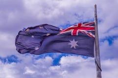 Bandiera australiana con il fondo del cielo blu immagini stock