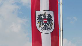 Bandiera austriaca con l'emblema che ondeggia in vento, fondo del cielo blu video d archivio