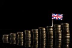 Bandiera BRITANNICA con il lotto delle monete sul nero Immagine Stock Libera da Diritti