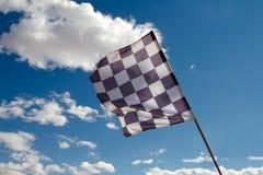 Bandiera Checkered contro il cielo blu fotografia stock