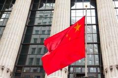 Bandiera cinese che galleggia davanti ad una costruzione di governo immagini stock