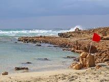 Bandiera d'avvertimento rossa su una spiaggia pietrosa durante la tempesta con le onde di rottura immagine stock libera da diritti