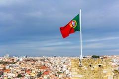 Bandiera d'ondeggiamento del Portoghese sopra il san Jorge Castle a Lisbona Fotografia Stock Libera da Diritti