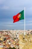 Bandiera d'ondeggiamento del Portoghese sopra il san Jorge Castle a Lisbona Immagini Stock