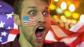 Bandiera d'ondeggiamento dell'uomo americano felice, celebrante vittoria nazionale della squadra di football americano stock footage
