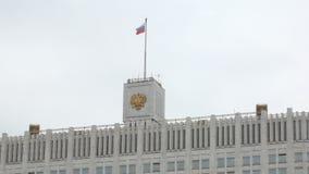 Bandiera d'ondeggiamento di Federazione Russa e della cresta sopra costruzione nel giorno nuvoloso stock footage