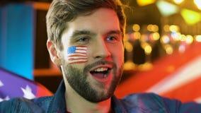 Bandiera d'ondeggiamento sorridente dell'uomo americano, celebrante festa nazionale, festa dell'indipendenza video d archivio