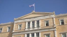 Bandiera d'ondeggiamento sulla costruzione greca del Parlamento a Atene, Grecia stock footage