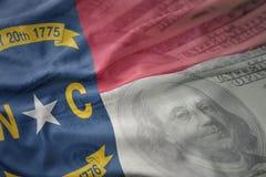 Bandiera d'ondeggiamento variopinta dello stato di North Carolina su un fondo americano dei soldi del dollaro immagini stock