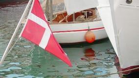 Bandiera danese che ondeggia davanti alle barche su un canale stock footage
