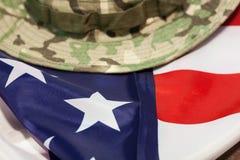 Bandiera degli Stati Uniti con il cappello di combattimento del cammuffamento Fotografia Stock