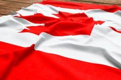 Bandiera del Canada su un fondo di legno dello scrittorio Vista superiore della bandiera canadese di seta immagini stock libere da diritti