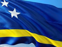 Bandiera del Curacao che ondeggia nel vento contro il cielo blu profondo Tessuto di alta qualit? fotografia stock