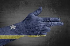 Bandiera del Curacao dipinta sulla mano maschio come una pistola immagine stock libera da diritti