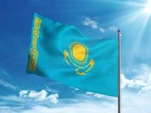 Bandiera del Kazakistan che ondeggia nel cielo blu Immagine Stock