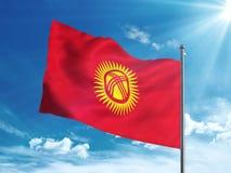 Bandiera del Kirghizistan che ondeggia nel cielo blu Fotografia Stock