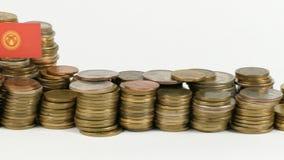 Bandiera del Kirghizistan con la pila di monete dei soldi video d archivio