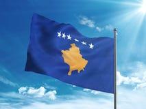 Bandiera del Kosovo che ondeggia nel cielo blu Immagine Stock Libera da Diritti