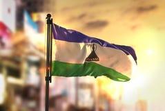 Bandiera del Lesotho contro fondo vago città ad alba Backligh immagini stock libere da diritti