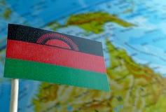 Bandiera del Malawi con una mappa del globo come fondo Fotografia Stock Libera da Diritti