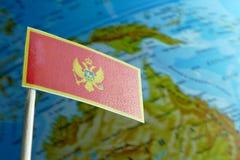 Bandiera del Montenegro con una mappa del globo come fondo Fotografie Stock