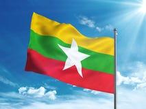 Bandiera del Myanmar che ondeggia nel cielo blu Fotografie Stock Libere da Diritti
