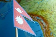 Bandiera del Nepal con una mappa del globo come fondo Fotografia Stock