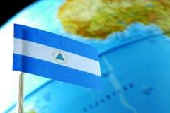 Bandiera del Nicaragua con una mappa del globo come fondo Fotografia Stock