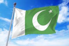 Bandiera del Pakistan che si sviluppa contro un cielo blu Fotografie Stock Libere da Diritti