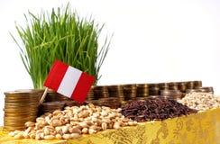Bandiera del Perù che ondeggia con la pila di monete dei soldi ed i mucchi di grano Fotografia Stock Libera da Diritti