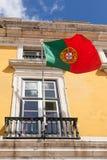 Bandiera del Portogallo che ondeggia sul vento nella parte anteriore un buil amministrativo Fotografia Stock