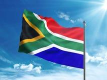 Bandiera del Sudafrica che ondeggia nel cielo blu Fotografie Stock Libere da Diritti