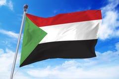Bandiera del Sudan che si sviluppa contro un cielo blu Fotografie Stock Libere da Diritti